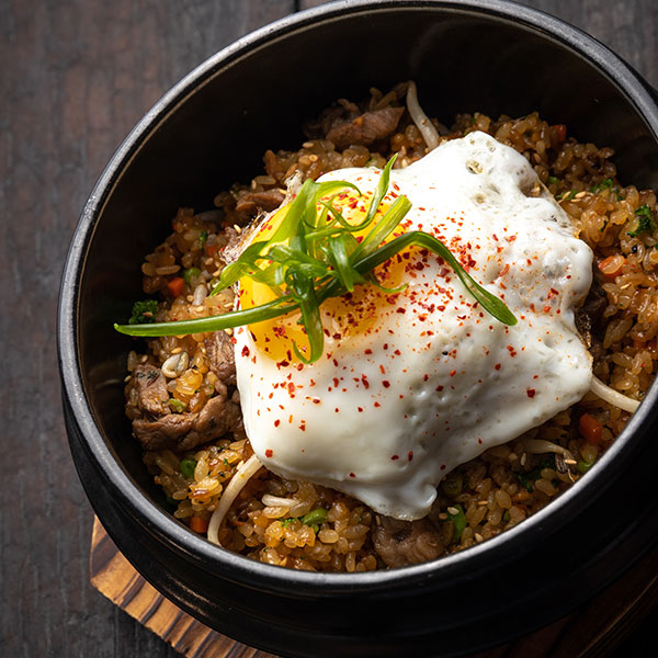 fried rice in bowl with fried egg on top, on wooden table
